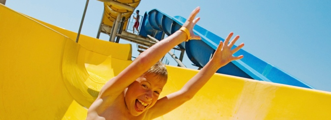 Young boy on bright yellow water slide waterslide